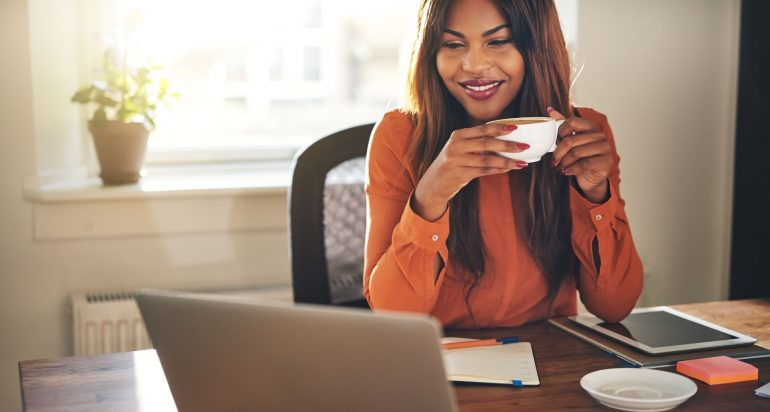 A woman sitting at a desk with a computer and a cup of coffee