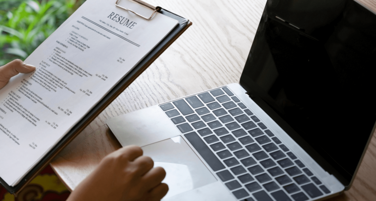 An individual looks at a resume while using a laptop