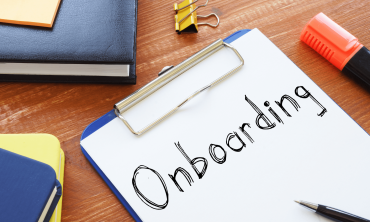 """The word """"onboarding"""" written on a paper attached to a clipboard."""