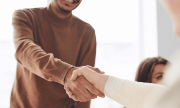 A newly hired employee shaking hands with a hiring manager